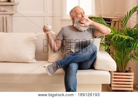 Senior Bearded Man Yawning With Coffee Cup And Laptop While Sitting On Sofa At Home
