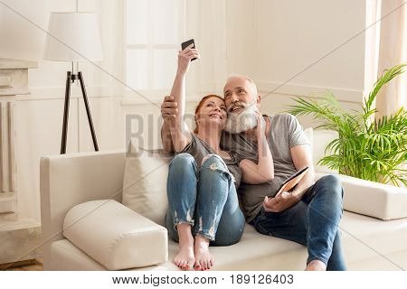 Happy Mature Couple Taking Selfie While Sitting On Sofa At Home
