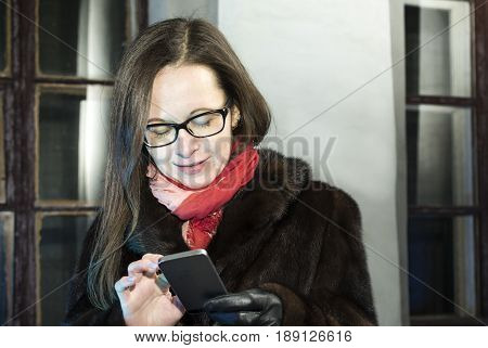 Female in fur coat and long dark hair chatting on a mobile phone night winter scene