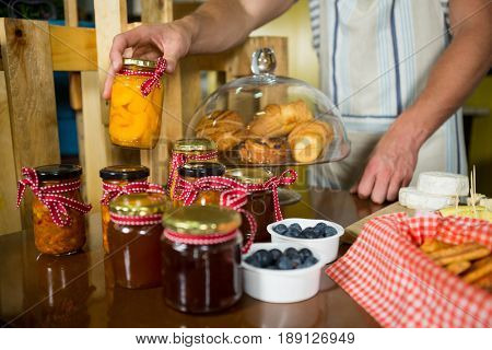 Shop assistant arranging jam and pickle jars in grocery shop