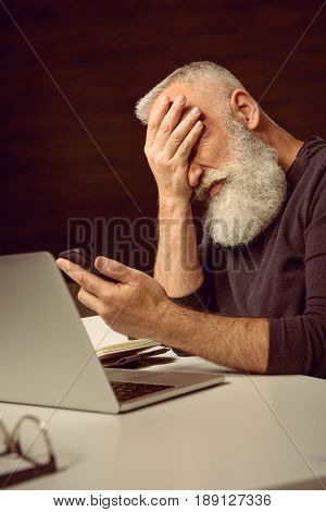 Grey Haired Man Sitting At Table And Holding Smartphone With Facepalm At Home