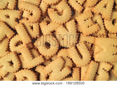 Top view of the word I LOVE U spelled with alphabet shaped biscuits on the pile of same biscuits