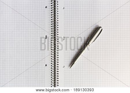 An Open Notebook In A Cage With Pen Close Up