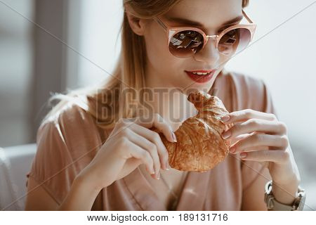 Attractive Caucasian Girl In Sunglasses With Croissant In Cafe, Having Lunch Concept