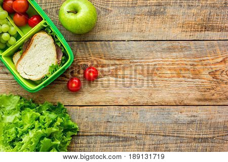 healthy food in lunchbox for dinner at school on wooden table background top view mockup