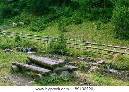 wooden table and bench. place for hikers to rest at the mountains near mountain stream with decorative wooden fence