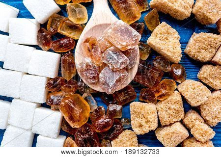 lumps of sugar for cooking sweets on blue kitchen table background top view pattern