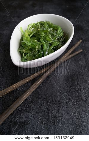 The Seaweed Salad In Ceramic Bowl With Japanese Chopsticks.