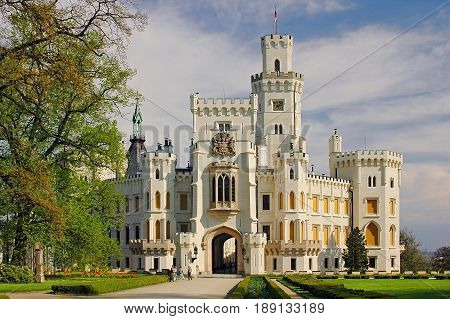 View on classic traditional white knight castle zamek Hluboka nad Vltavou, castle park garden. Classic knight castle gate, walls and towers. Famous european Czech Republic castles sghtseeing tours