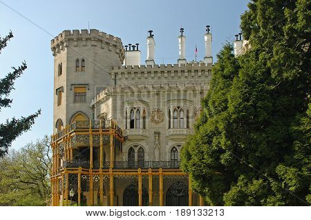 View on classic traditional white knight castle zamek Hluboka nad Vltavou, castle park garden. Classic knight walls and towers. Famous european Czech Republic castles sghtseeing tours. Garden view