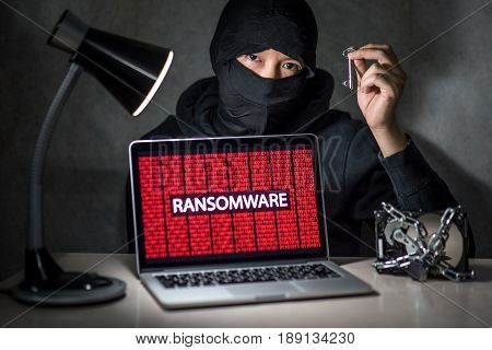 Hacker holding the key with laptop computer screen showing ransomware attacking alert in red digital binary background with hard disk drive lock. Cyber attack concept