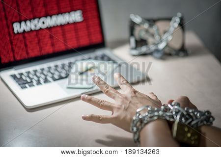 Hands tied up by chains and lock Hard disk file locked with monitor show ransomware cyber attack internet security breaches on laptop computer