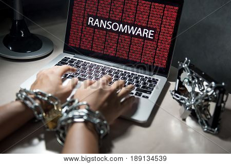 user hand tied up by chains and lock Hard disk file locked with monitor show ransomware cyber attack internet security breaches on computer laptop