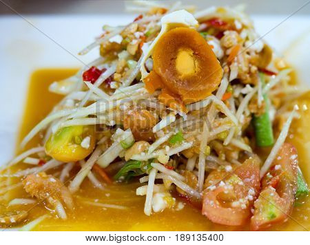 Green papaya salad or Som tum with preserved egg. Popular Thai local food. Spicy salad from shredded unripe papaya sliced tomatoes raw yardlong beans peanuts dried mini shrimp and fresh garlic.