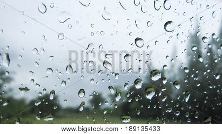 Raindrops on the car glass. Water drops at the car glass and wing mirror after heavy rains.