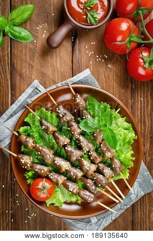 Chicken hearts on a barbecue sticks topped with sesame seeds served on wooden rustic table. Barbecue lunch