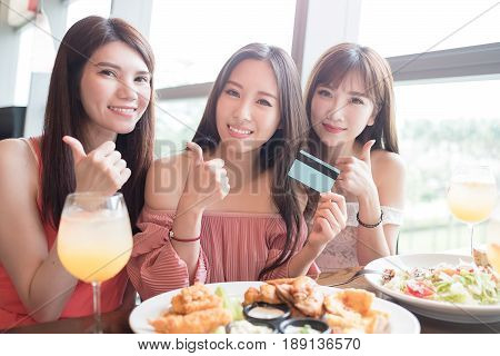 beauty women take credit card and thumb up in restaurant