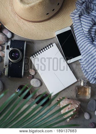 Flat lay, top view traveler's table desk floor. Workspace with notebook, diary, straw hat and sun glasses, vintage camera, striped silk scarf, perfume bottle, pebbles with shell, tropical palm leaves