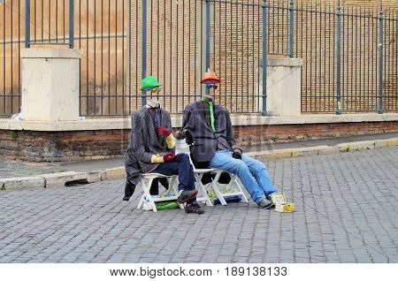two sitting men with red and green hat but without faces (joke)