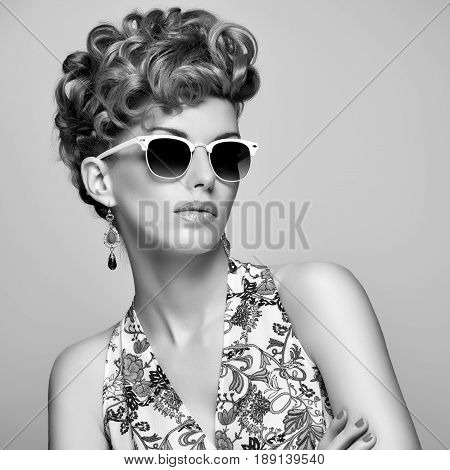Fashion Portrait Model in Sexy Dress. Stylish Mohawk hairstyle, fashion Makeup. Beauty woman in Trendy Sunglasses, Glamour Lady, fashion pose. Playful Girl, Luxury summer Accessories.Black and white