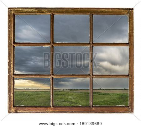 heavy storm clouds and rain over Nebraska farmland as seen  through vintage, grunge, sash window with dirty glass