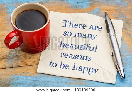 There are some many beautiful reasons to be happy - handwriting on a napkin with a cup of coffee