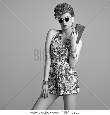 Fashion Model in Sexy Jumpsuit. Stylish Mohawk hairstyle. Beauty woman in Trendy Summer Dress, fashion Makeup, Floral Outfit.Glamour Lady, fashion pose. Playful Girl, Luxury Accessories. Black and White
