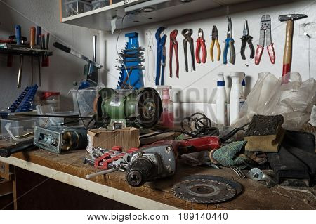 Messy workshop complete chaos on workbench unorganised basement or garage. Efficiency and arrangement in workshop time to sort out mess concept.