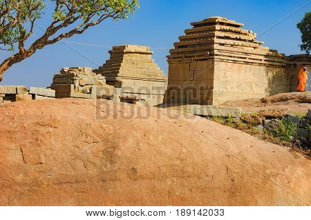 View of ancient ruins on Hemakuta hill in Hampi, Karnataka, India. Landscape with amazing stones tropical nature and temple under the blue sky. Monk stands near the ruins in orange robes