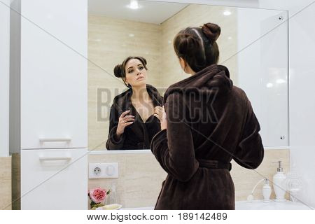 Woman In A Brown Cosy Bathrobe In The Bathroom