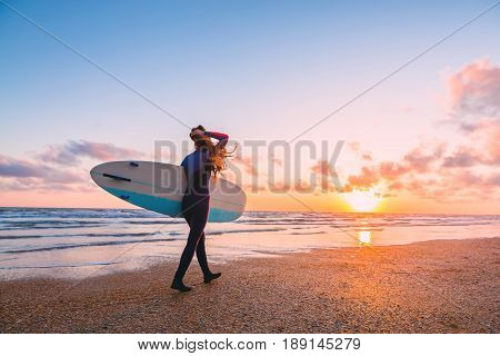 Sporty surf girl go to surfing. Woman with surfboard and sunset or sunrise on ocean