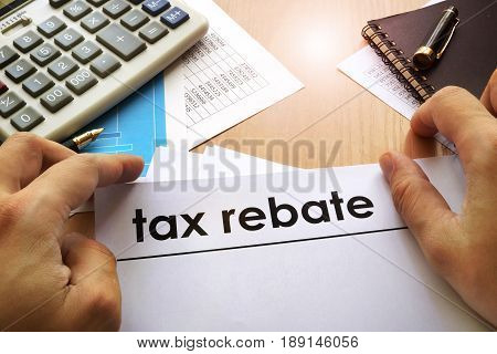 Hands holding documents with title tax rebate.