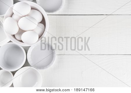 White Ramekins on White Wood Table with copy space. One dish is filled with eggs.
