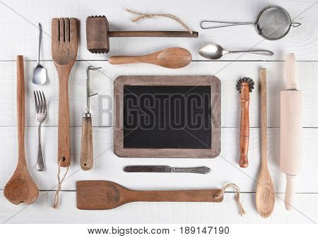 Top view of a group of cooking utensils on a rustic wood kitchen table arranged around a blank chalk board.