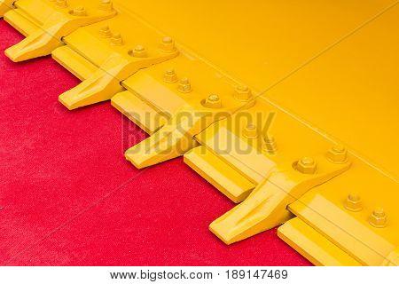 Bucket teeth of excavator on red carpet
