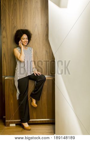 Smiling African American Businesswoman Using Mobile Phone In Office
