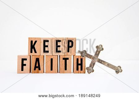 Keep Faith in wooden block letters with silver cross on white background