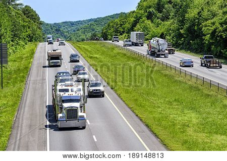 A steady mix of trucks cars and SUVs roll down an interstate highway in eastern Tennessee. Heat rising from the pavement gives a cool shimmering effect to vehicles and forest in the distance.