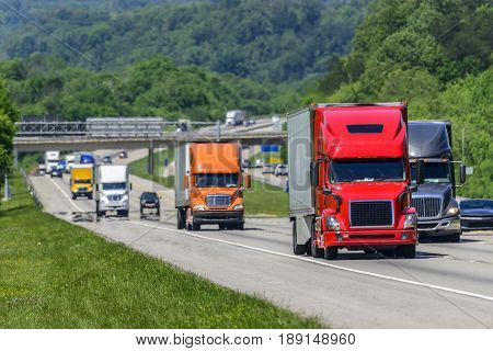 A steady flow of semis lead the way down a busy interstate highway in Tennessee. Heat waves rising from the pavement give a nice shimmering effect to vehicles and forest behind the lead trucks. Excellent reverse copy space across both top and bottom of im