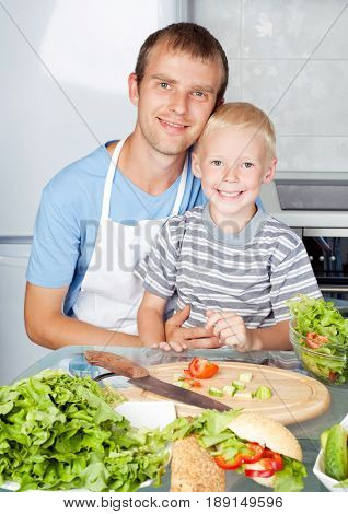 happy young father cooking with his son at home