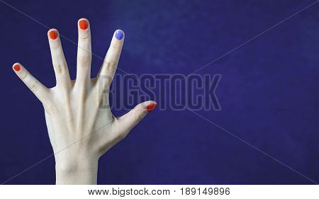 One different nail color in finger in caucasian hand. Red and blue painted fingernails. Dare to be different, originality and creativity concept with blue background. Stand out from the crowd.