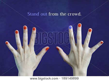 Stand out from the crowd. Originality and creativity concept with blue background. One different nail color in finger in caucasian hands. Red and blue painted fingernails. Dare to be different