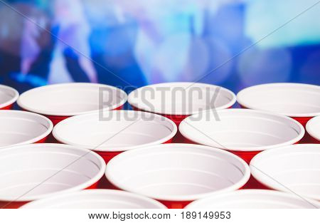 Many red party cups with blurred celebrating people in the background. Low angle close up of college alcohol containers. Marketing and promotion for events or beer pong tournament. College celebration