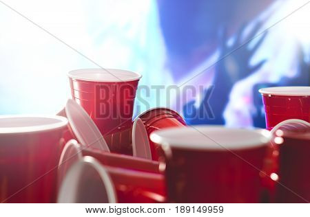 Many red party cups with blurred celebrating people in the background. College alcohol containers in mixed positions. Marketing and promotion for events or beer pong tournament.