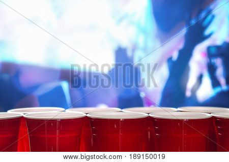 Plastic red party cups in a row in a nightclub full of people dancing on the dance floor in the background. Perfect for marketing and promotion for events or beer pong tournament. College celebration.