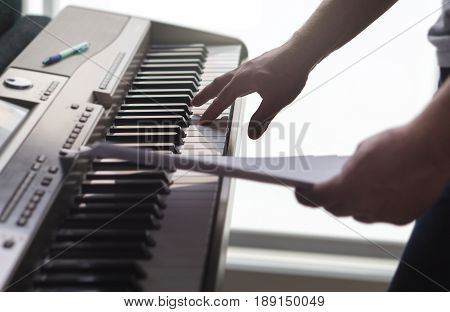 One single finger pressing key on piano. Man looking at paper notes and training a new song or melody from the sheet music. Pianist composing new work or creative producer working in home studio.