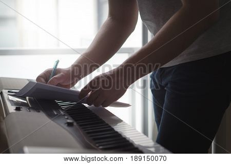 Composer and songwriter writing notes or lyrics on paper on piano. Musician write a song in home studio on an digital instrument. Excited about new idea or melody. Shadowy dark ambient lightning.