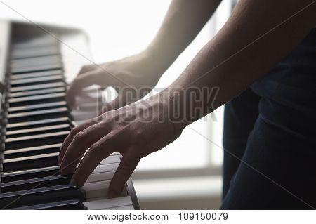 Man playing piano standing in home studio. Ambient mood with sun light. Close up of male hands on keys of electronic keyboard. Person play digital instrument in dark shadowy lighting. Music concept.