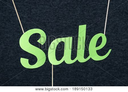 Sale text hanging from ceiling by wooden stick. Vibrant summer design for marketing in website or social media. Green handcraft letters cut from cardboard paper. Special bargain campaign and offer.
