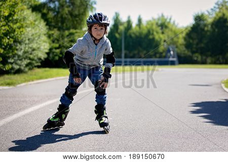 Cute Little Child, Boy, Riding On A Rollerblades In The Park